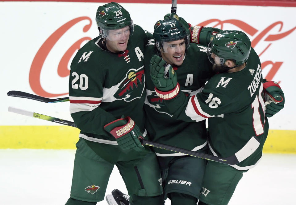 FILE - Minnesota Wild's Ryan Suter (20) and Jason Zucker (16) congratulate left wing Zach Parise (11) on his goal against the Arizona Coyotes during the third period of an NHL hockey game in St. Paul, Minn., in this Thursday, Nov. 14, 2019, file photo. After signing with Minnesota together, Zach Parise and Ryan Suter are being bought out together. The Wild announced Tuesday, July 13, 2021, that the team is buying out the final four years of each player's contract, a stunning move early in the NHL offseason. (AP Photo/Hannah Foslien, File)