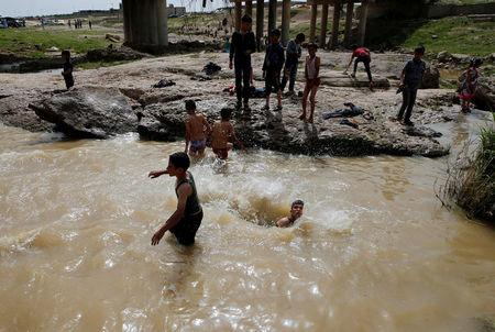 "Iraqi youths swim as they enjoy their Friday holiday at Shallalat district (Arabic for ""waterfalls"") in eastern Mosul, Iraq, April 21, 2017. REUTERS/ Muhammad Hamed"