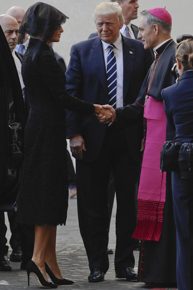 First lady Melania Trump, left, flanked by her husband the US President Donald Trump, greets Monsignor Georg Gaenswein as she arrives at the San Damaso courtyard for her private audience with Pope Francis, at the Vatican, Wednesday, May 24, 2017. Melania turned to one of her favorite fashion houses, Dolce & Gabbana, for her audience with the pope and her arrival in Italy. (AP Photo/Gregorio Borgia)