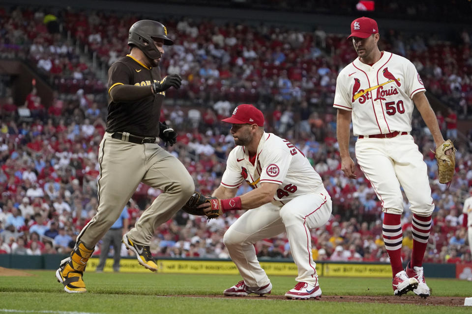 San Diego Padres' Victor Caratini, left, is tagged out by St. Louis Cardinals first baseman Paul Goldschmidt as Cardinals pitcher Adam Wainwright (50) watches during the third inning of a baseball game Saturday, Sept. 18, 2021, in St. Louis. (AP Photo/Jeff Roberson)