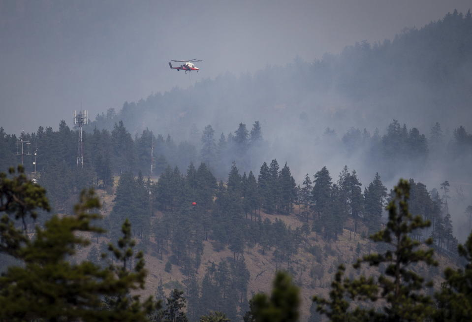 A helicopter pilot prepares to drop water on a wildfire burning in Lytton, British Columbia, on Friday, July 2, 2021. (Darryl Dyck/The Canadian Press via AP)