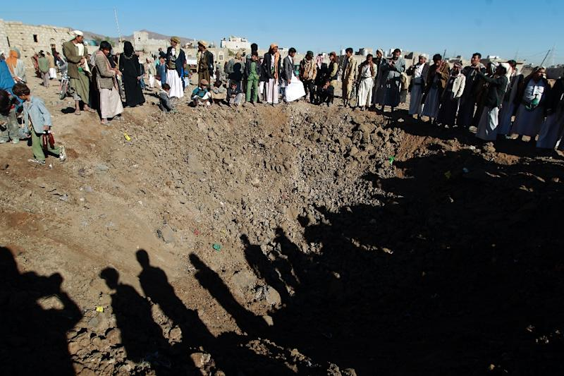 Yemenis gather around a crater reportedly caused by a Saudi-led airstrike on the outskirts of the capital Sanaa on December 29, 2015