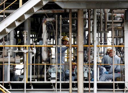 Workers repair a facility of a chemical factory at the Keihin Industrial Zone in Kawasaki