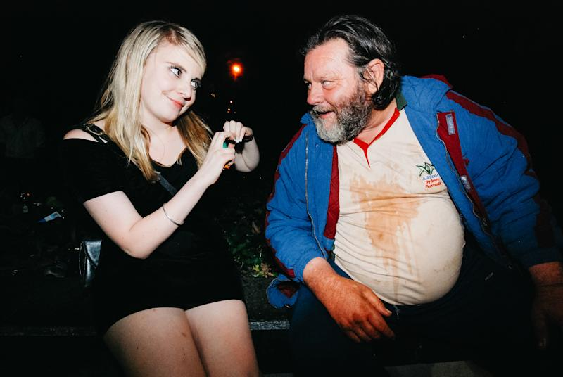 A young girl smiles at a homeless man.