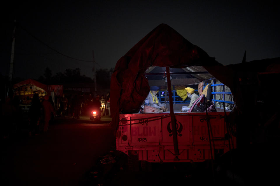 "Karmat Singh, 62, right, and Joginder Singh, 77, pray inside their tractor trailer parked on a highway as they join a protest against new farm bills, at the Delhi-Haryana state border, India, Wednesday, Dec. 2, 2020. The convoy of trucks, trailers and tractors stretches for at least three kilometers (1.8 miles) with farmers who have hunkered down, supplied with enough food and fuel to last weeks. Their rallying call is ""Inquilab Zindabad"" (""Long live the revolution""). (AP Photo/Altaf Qadri)"