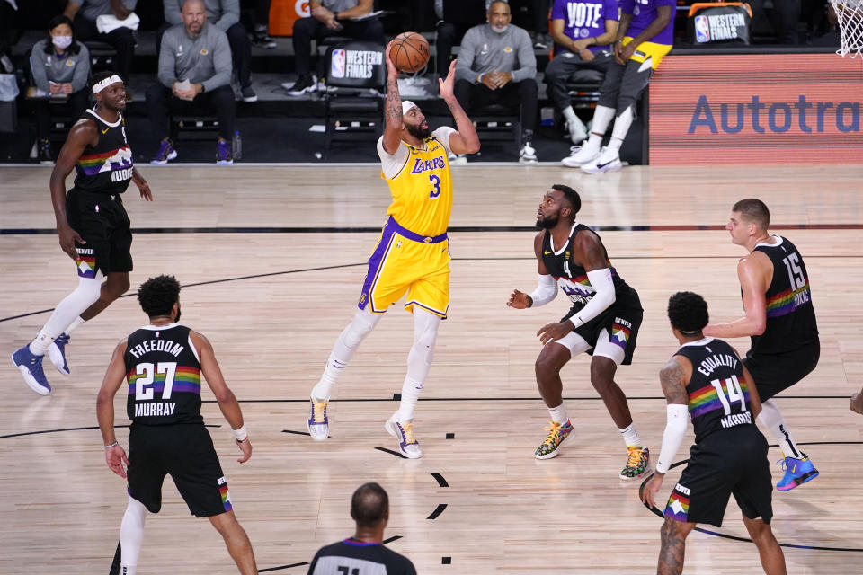 Los Angeles Lakers' Anthony Davis (3) drives against Denver Nuggets' Paul Millsap (4) during the first half of an NBA conference final playoff basketball game Thursday, Sept. 24, 2020, in Lake Buena Vista, Fla. (AP Photo/Mark J. Terrill)