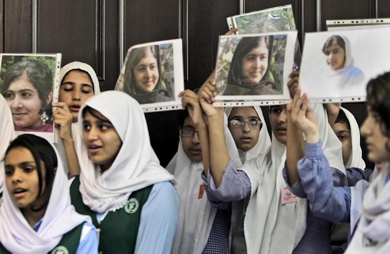 Pakistani students sing as they hold pictures of 14-year-old schoolgirl Malala Yousufzai, who was shot last Tuesday by the Taliban for speaking out in support of education for women, during a tribute at the Pakistani Embassy in Abu Dhabi, United Arab Emirates, Monday, Oct. 15, 2012. Pakistan airlifted a 14-year-old activist who was shot and seriously wounded by the Taliban to the United Kingdom for treatment Monday, a move that will give her access to the specialized medical care she needs to recover and also protect her from follow-up attacks threatened by the militants. (AP Photo/Kamran Jebreili)