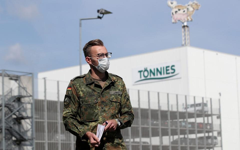 Mandatory Credit: Photo by FRIEDEMANN VOGEL/EPA-EFE/Shutterstock (10684765f) A German armed forces (Bundeswehr) soldier wearing a face mask arrives at the headquarters of the company Toennies, Europe's biggest slaughterhouse, where the troops are helping to set up a coronavirus testing center, in Rheda-Wiedenbrueck, western Germany, 19 June 2020. According to media reports, at least 650 Toennies employees at the Rheda-Wiedenbrueck plant have tested positive for the SARS-CoV-2 coronavirus that causes the COVID-19 disease, making it one of the largest clusters of the ongoing pandemic detected so far in the country. German army helps set up coronavirus testing center at Toennies meat factory, Rheda Wiedenbrueck, Germany - 19 Jun 2020 - FRIEDEMANN VOGEL/EPA-EFE/Shutterstock