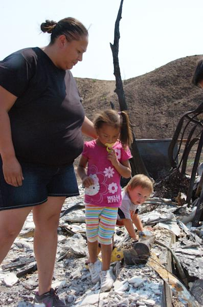 LuAnna Fox comforts her three-year-old daughter Kamille as her one-year-old son Jerrico looks on after Kamille's burned up Dora the Explorer lunch box was pulled from the ruins of the family's house on the Northern Cheyenne Indian Reservation in this Aug. 9 photograph. Wildfires have burned more than 90 square miles on the reservation since June. (AP Photo/Matthew Brown)