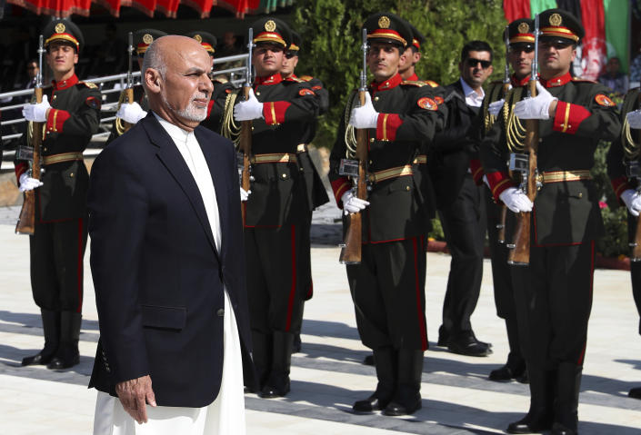 In this photo released by the Afghan Presidential Palace, Afghan President Ashraf Ghani inspects the honor guard during Independence Day celebrations at Defense Ministry in Kabul, Afghanistan, Monday, Aug. 19, 2019. Afghanistan's president is vowing to eliminate all safe havens of the Islamic State group as the country marks a subdued 100th Independence Day after a horrific wedding attack claimed by the local IS affiliate.(Afghan Presidential Palace via AP)
