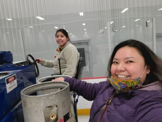 Recreation leader Rianna Camsell, left, learning how to drive a Zamboni with community government recreation manager Colinda Blondin, right, in Behchokǫ̀, N.W.T. (Photo courtesy of Colinda Blondin - image credit)