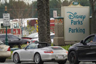 FILE - In this Jan. 13, 2021, file photo, vehicles queue up outside the Disneyland Resort parking lot for a COVID-19 vaccine in Anaheim, Calif. Event organizers and other unconventional logistics experts are using their skills to help the nation vaccinate as many people against COVID-19 as possible. Disneyland — hit hard by the global health crisis — is hosting a mass vaccination effort. (AP Photo/Damian Dovarganes, File)