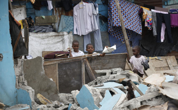 In this image taken Thursday Feb. 28, 2013 children stand on the rubble of a demolished house at Ijora Badia slum in Lagos, Nigeria. The bulldozers arrived at dawn to this neighborhood of shanty homes and concrete buildings in Nigeria's largest city, followed by police officers in riot gear carrying Kalashnikov assault rifles. The police banged on doors, corralling the thousands who live in Ijora-Badia off to the side as the bulldozers' blades tore through scrap-lumber walls, its track grinding the possessions inside into the black murk of swamp beneath it. It left behind only a field of debris that children days later picked through, their small hands dodging exposed rusty nails to pull away anything of value left behind. (AP Photo/Sunday Alamba)