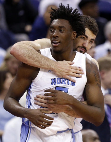 North Carolina's Luke Maye, back, and Nassir Little hug in the final seconds of the second half against Iona during a first round men's college basketball game in the NCAA Tournament in Columbus, Ohio, Friday, March 22, 2019. (AP Photo/Paul Vernon)
