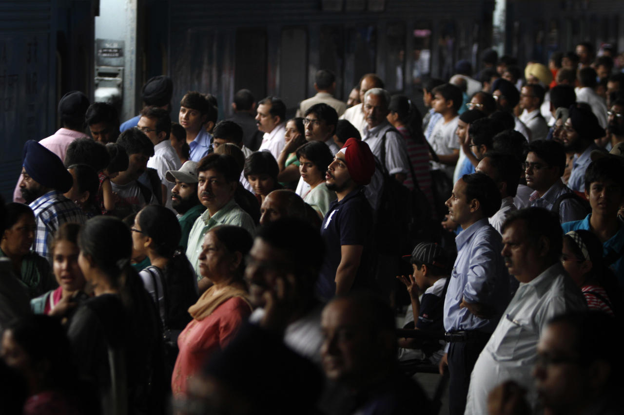 Stranded passengers wait for their power to get restore, at New Delhi railway station, in New Delhi, India, Monday, July 30, 2012. Northern India's power grid crashed Monday, halting hundreds of trains, forcing hospitals and airports to use backup generators and leaving 370 million people — more than the population of the United States and Canada combined — sweltering in the summer heat. (AP Photo/Rajesh Kumar Singh)
