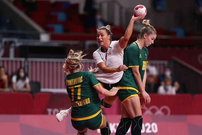 <p>Norway's Nora Moerk shoots at goal against Montenegro—with Majda Mehmedovic and Ema Ramusovic on the defense—during the women's preliminary handball match.</p>