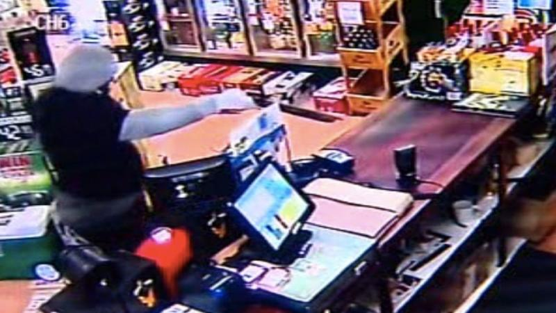 The armed assailant enters one shop armed with a gun. Photo: CCTV