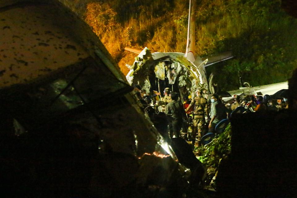 First responders inspect the wreckage of an Air India Express jet, which was carrying more than 190 passengers and crew from Dubai, after it crashed by overshooting the runway at Calicut International Airport in Karipur, Kerala, on August 7, 2020. - At least 14 people died and 15 others were critically injured when a passenger jet skidded off the runway after landing in heavy rain in India, police said on August 7. (Photo by Favas JALLA / AFP) (Photo by FAVAS JALLA/AFP via Getty Images)