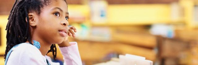 Contemplative girl writing notes in the classroom