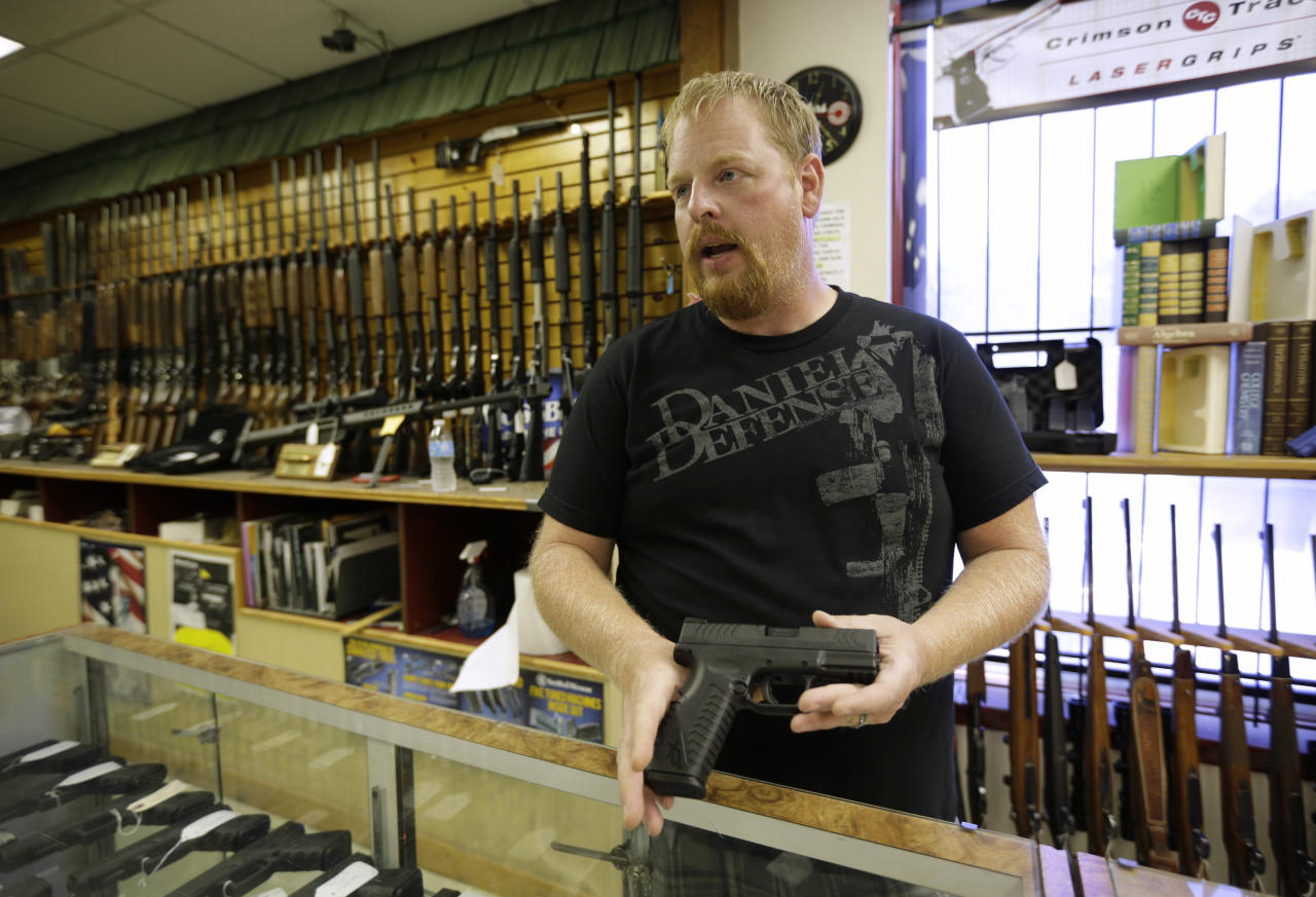 Eric Grabowski holds a hand gun, very similar to the gun used by alleged gunman Wade Michael Page, in The Shooter Shop, where Page purchased the weapon, in West Allis, Wisconsin, August 7, 2012. The gun used in the crime was the crime was identical, only it had a shorter barrel. The semiautomatic handgun used in the deadly attack on a Wisconsin Sikh temple is the same type used in other recent U.S. mass shootings, including one at a theater in Colorado, and the attack on a congresswoman in Arizona, gun experts said. REUTERS/John Gress (UNITED STATES - Tags: CRIME LAW RELIGION)