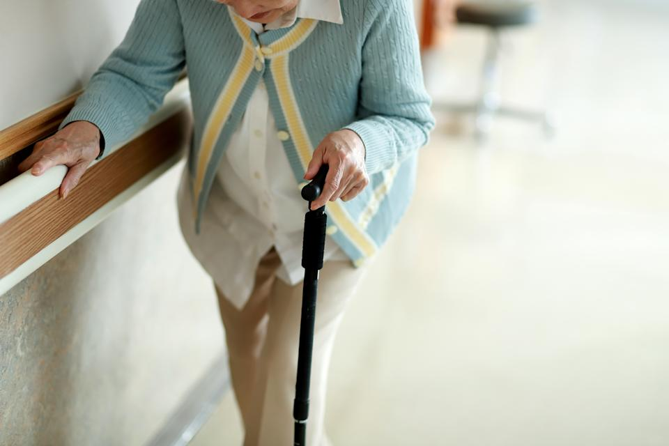 Elderly woman walking with a walking stick.