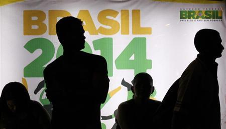 People are silhouetted in front of an advertisement of the Brazil 2014 FIFA Soccer World Cup as they wait for a bus in Recife