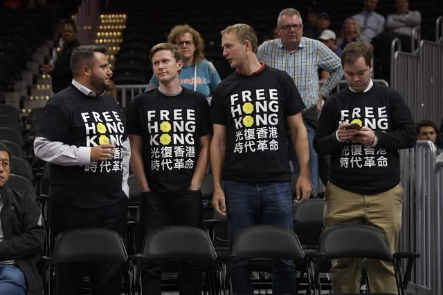 Activists wear Free Hong Kong T-shirts before an NBA exhibition basketball game between the Washington Wizards and the Guangzhou Loong-Lions in Washington