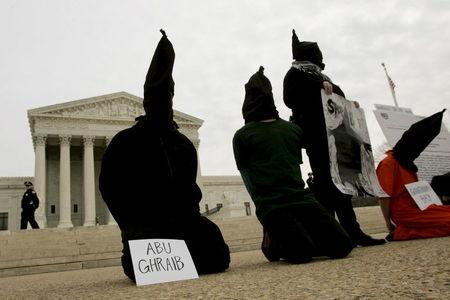"""District of Columbia Anti-War Network activists take part in a demonstration to oppose """"American violations of international human rights"""" at the Abu Ghraib prison in Iraq by U.S. military personnel in front of the U.S. Supreme Court in this February 9, 2005 file photo. REUTERS/Larry Downing/Files"""