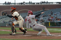 Cincinnati Reds' Jesse Winker (33) slides home to score past San Francisco Giants catcher Buster Posey during the second inning of a baseball game in San Francisco, Tuesday, April 13, 2021. (AP Photo/Jeff Chiu)
