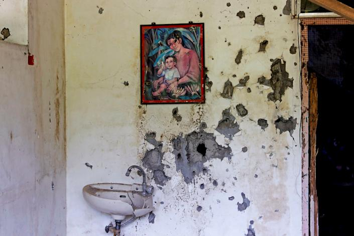 A painting of a mother and a child hangs on a wall at a bullet-riddled structure in Marawi City, Lanao del Sur province, Philippines. (Photo: Eloisa Lopez/Reuters)