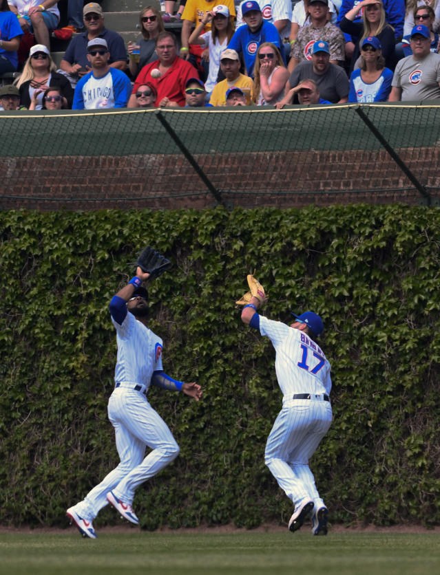 Chicago Cubs center fielder Jason Heyward, left, and right fielder Kris Bryant (17) both eye the ball before colliding while chasing a ball hit by Cincinnati Reds'c Eugenio Suarez (7) during the sixth inning of a baseball game Sunday, May 26, 2019, in Chicago. Bryant was charged with an error on the play. (AP Photo/Matt Marton)