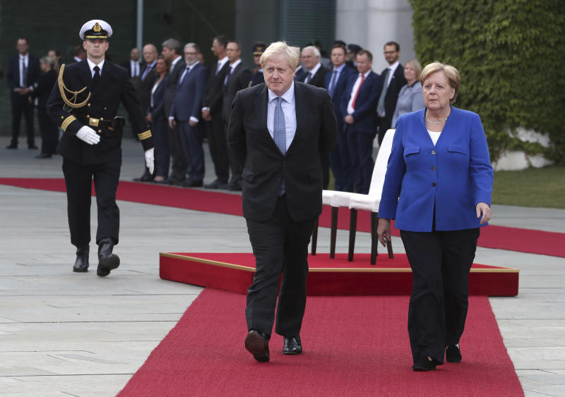 German Chancellor Angela Merkel welcomes Britain's Prime Minister Boris Johnson with military honors for a meeting at the Chancellery in Berlin, Germany, Wednesday, Aug. 21, 2019. (AP Photo/Michael Sohn)