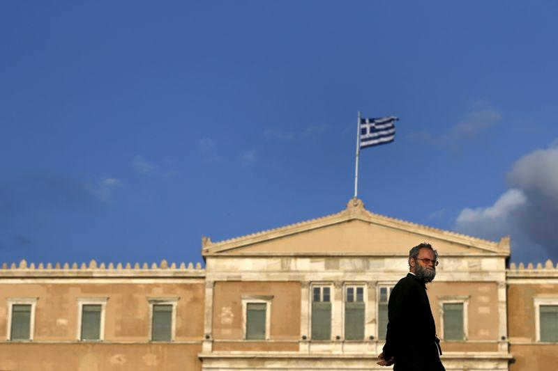 Orthodox priest walks in front of the parliament building in Athens