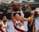 Portland Trail Blazers center Enes Kanter, middle, and Utah Jazz center Rudy Gobert, right, reach for a rebound as Trail Blazers guard Gary Trent Jr. watches during the first half of an NBA basketball game in Portland, Ore., Wednesday, Dec. 23, 2020. (AP Photo/Steve Dipaola)