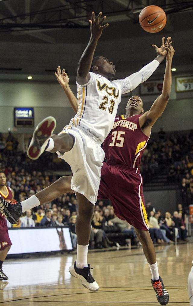 VCU forward Jarred Guest, left, and Winthrop forward Jarad Scott, right, stretch for a rebound during the first half of an NCAA college basketball game in Richmond, Va., Saturday, Nov. 16, 2013. (AP Photo/Zach Gibson)