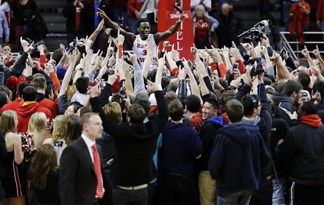 Illinois State guard Daishon Knight (3) celebrates with teammates and fans after students stormed the court for Illinois State's 81-75 win against Dayton in an NCAA college basketball game Saturday, Dec. 7, 2013, in Normal, Ill. (AP Photo/ Stephen Haas)