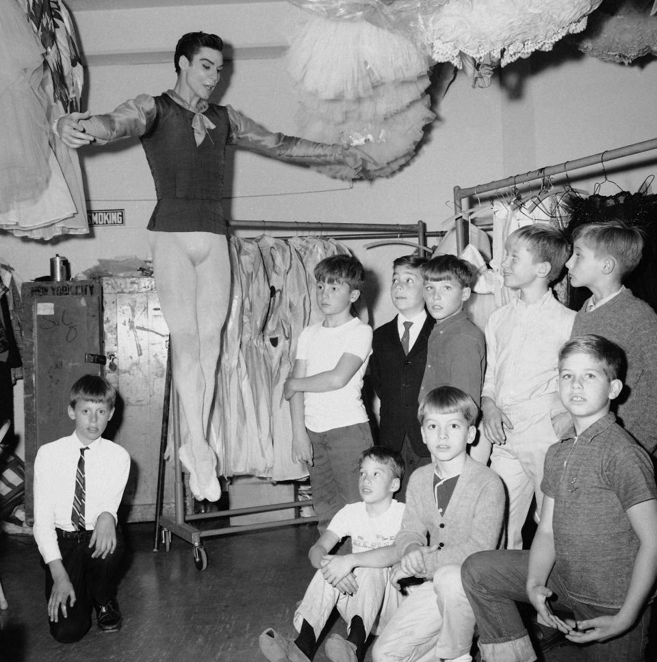 FILE - Jacques d'Amboise, principal dancer of the New York City ballet, demonstrates a jump to his young students backstage at New York's Lincoln Center on Oct. 30, 1965. D'Amboise, who grew up on the streets of upper Manhattan to become one of the world's premier classical dancers at New York City Ballet and spent the last four and a half decades providing free dance classes to city youth at his National Dance Institute, died Sunday, May 2, 2021. He was 86. His death was confirmed by Ellen Weinstein, director of the institute. (AP Photo, File)