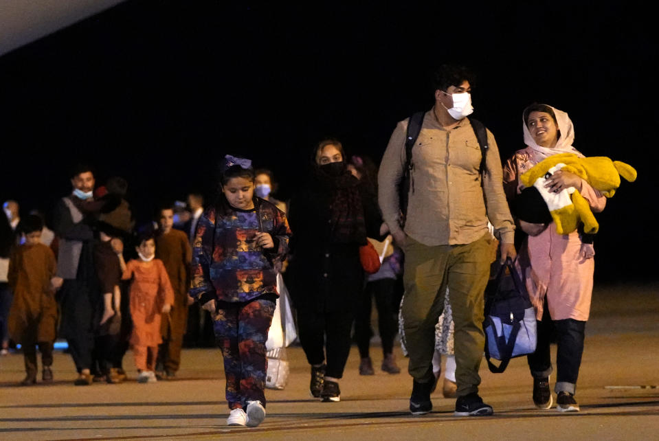 Afghan people who were transported from Islamabad, walk after disembarking a plane, at the Torrejon military base in Spain on Monday, Oct. 11, 2021. (AP Photo/Manu Fernandez)