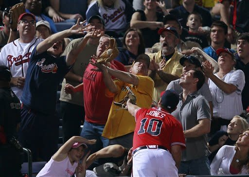 A spectator catches a foul ball off the bat of Pittsburgh Pirates' Garrett Jones as Atlanta Braves third baseman Chipper Jones (10) looks on in the fourth inning of a baseball game on Friday, April 27, 2012, in Atlanta. (AP Photo/John Bazemore)