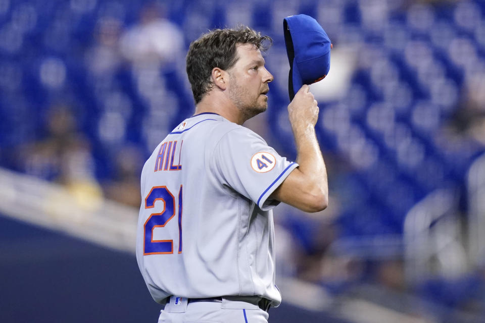 New York Mets starting pitcher Rich Hill adjusts his cap after walking Miami Marlins' Joe Panik during the fourth inning of a baseball game, Thursday, Aug. 5, 2021, in Miami. (AP Photo/Lynne Sladky)