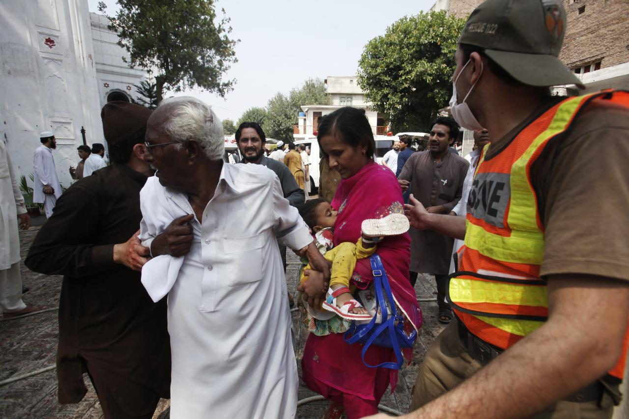 Rescue workers escort a woman carrying a dead child from the site of a blast at a church in Peshawa