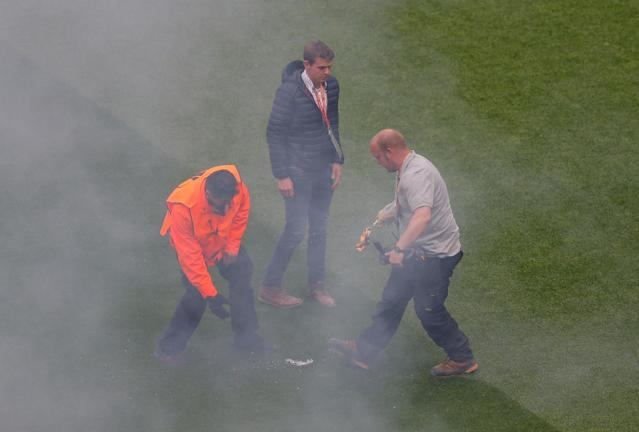Soccer Football - Europa League Final - Olympique de Marseille vs Atletico Madrid - Groupama Stadium, Lyon, France - May 16, 2018 Staff remove a flare that was thrown on the pitch from outside the stadium before the match REUTERS/Vincent Kessler