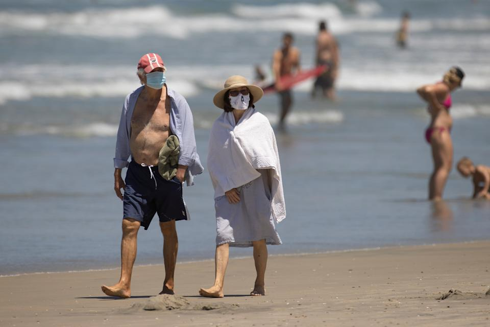 People wearing face masks walk along the beach as California reported its largest number of new coronavirus infections in a single day, during the outbreak of the coronavirus disease (COVID-19) in Del Mar, California, U.S., July 15, 2020. REUTERS/Mike Blake