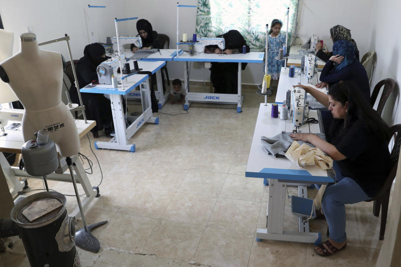 In this Monday, June 17, 2019 photo, Syrian refugees work sewing at a workshop in the town of Bar Elias, Bekaa Valley, Lebanon. Authorities in Lebanon are waging their most aggressive campaign yet against Syrian refugees, making heated calls for them to go back to their country and taking action to ensure they can't put down roots. They are shutting down shops where Syrians work without permits and ordering the demolition of anything in their squalid camps that could be a permanent home. (AP Photo/Bilal Hussein)