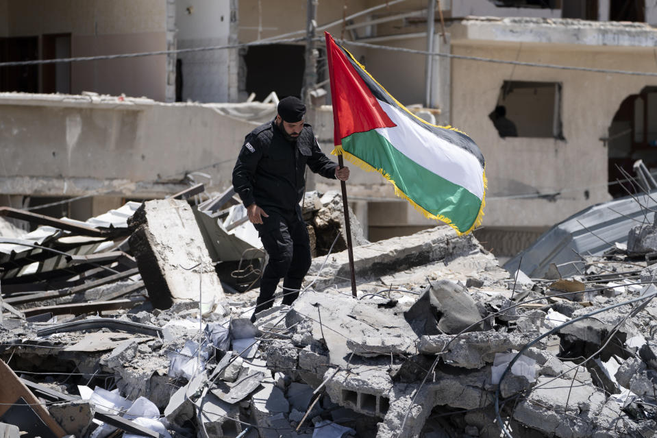 A Hamas police officer removes a Palestinian flag that was placed atop a debris pile of a station building previously destroyed in an airstrike before a news conference following a cease-fire reached after an 11-day war between Gaza's Hamas rulers and Israel, in Gaza City, Saturday, May 22, 2021. (AP Photo/John Minchillo)