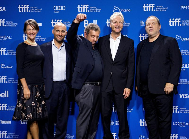 """Filmmakers for """"12.12.12: The Concert for Sandy Relief,"""" from left, producers Meghan O'Hara and Amir Bar-Lev and executive producers James Dolan, John Sykes and Harvey Weinstein pose for a picture during a photo call for the documentary at the 2013 Toronto International Film Festival in Toronto on Monday, Sept. 9, 2013. (AP Photo/The Canadian Press, Galit Rodan)"""