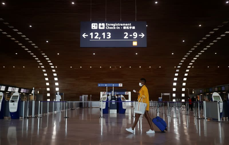 A woman makes her way in the departures area of the Terminal 2E at Charles-de-Gaulle airport in Roissy
