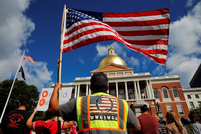 A man wearing a QAnon vest holding an American flag demonstrates outside the State House in Boston, Mass.