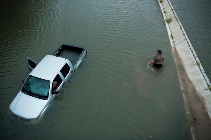 A truck driver walks past an abandoned truck while checking the depth of the water at an underpass in Houston.