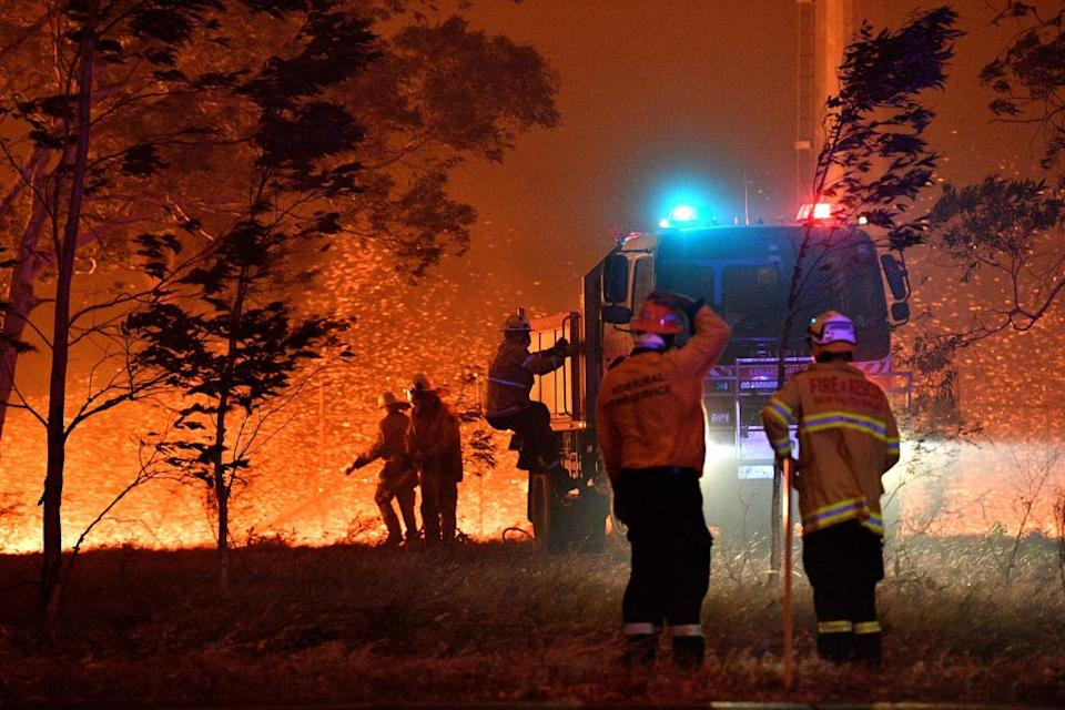 Firefighters hose down trees as they battle against bushfires around the town of Nowra on December 31, 2019. Source: Getty